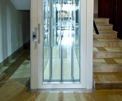 Ascenseur vitré en copropriété et habillage blanc